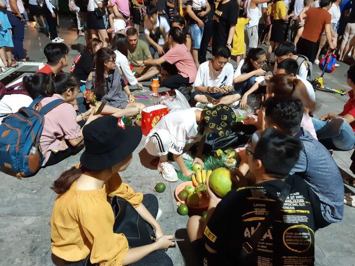 Nhiều người ngồi ngay ngoài lòng đường ăn uống.