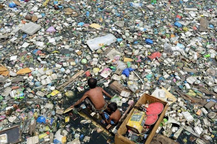 Hai cha con đang chèo ghe qua một con sông được phủ đầy bề mặt bởi rác thải, họ đồng thời cũng đang làm công việc thường ngày của mình đó chính là thu lượm số rác thải này và bán lại cho các cơ sở tái chế trong vùng. Ảnh: Noah Cellis/Stringer.