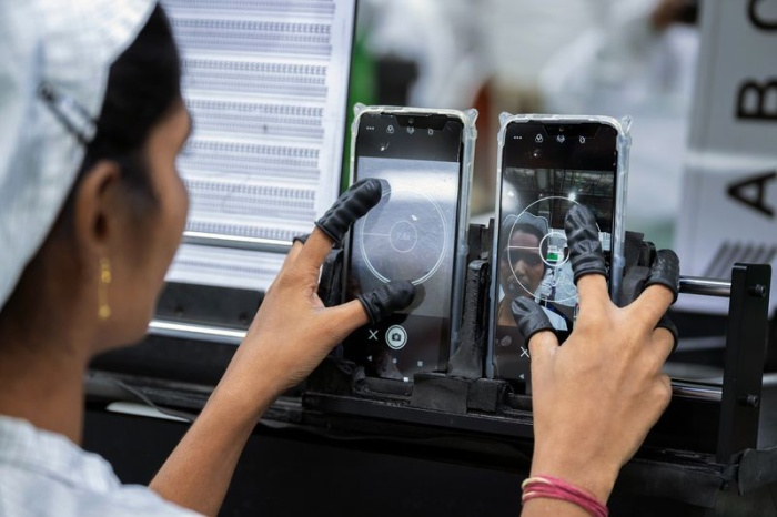 Một nhân viên kiểm tra camera trên điện thoại. (Ảnh: Karen Dias/Bloomberg)