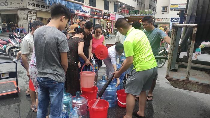 Người dân mang theo đủ loại xô, chậu, can nhựa để chứa nước.