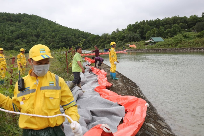 Những chiếc lưới lọc dầu đang được kĩ thuật viên của Trung tâm ứng phó sự cố môi trường Việt Nam lắp đặt trước khi đưa xuống lòng hồ chứa.