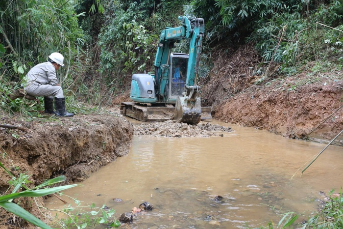 Máy xúc được huy động nạo vét khu vực suối bị tràn dầu thải.