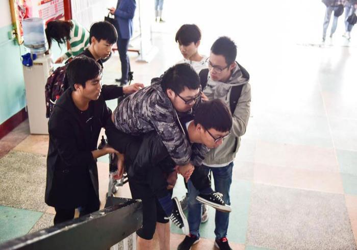 Các bạn học thay nhau cõng Liu tới lớp.
