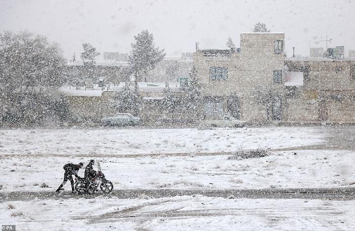 Hình ảnh hai con người nhỏ bé và một chiếc xe mô tô giữa trời bão tuyết. Bức ảnh về nhì trong hạng mục Nhiếp ảnh gia trẻ