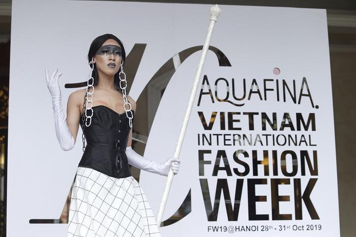Đi cùng Mèo Thoại đến Aquafina Tuần lễ quốc tế thời trang Việt Nam 2019 là tín đồ thời trang tự làm trang phục bằng rèm cửa. Phụ kiện khuyên tai và gậy đi kèm cũng là sản phẩm tự chế.