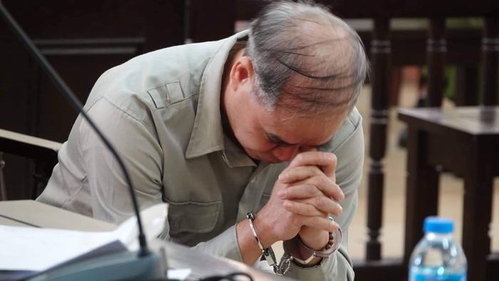 Bị cáo cúi mặt trong lúc chờ xét xử.