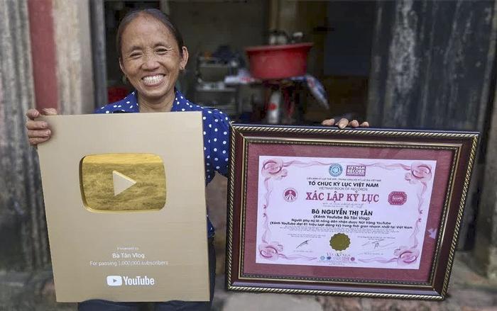 Bà Tân Vlog bên cạnh nút vàng YouTube và giấy xác lập kỷ lục Guinness Việt Nam.