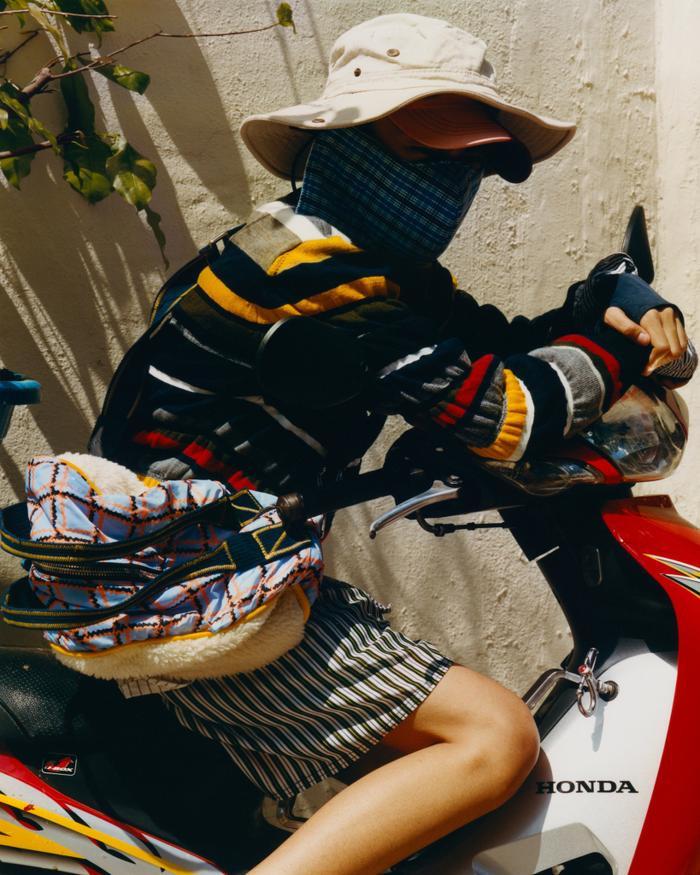 Chỉ có hai thương hiệu góp mặt trong bức ảnh này nhưng giá tiền thì sốc không kém: chiếc áo len có giá 1.250 USD cùng chiếc túi 850 USD được mặc cùng với nón vải, khẩu trang và quần đùi một thoáng quê nhà. Theo chia sẻ của tác giả, những nam người mẫu trong bộ ảnh đều làm lao động tại các khu chợ trong thành phố, ngoài Chợ Bà Chiểu còn có Chợ Lớn, Chợ Bến Thành.