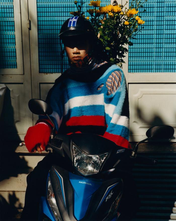 Bên dưới chiếc nón bảo hiểm dùng để lao động hằng ngày là chiếc áo len rách vai được bán với giá 513 USD cùng chiếc áo 370 USD bên trong. Nhà thiết kế Jason Rider tự thấy có chút ngớ ngẩn khi kết hợp những món đồ may mặc như thế này lại với nhau, nhưng anh cho biết anh thích nhìn một Sài Gòn mới lạ như vậy vì nó tươi mới và đẹp.