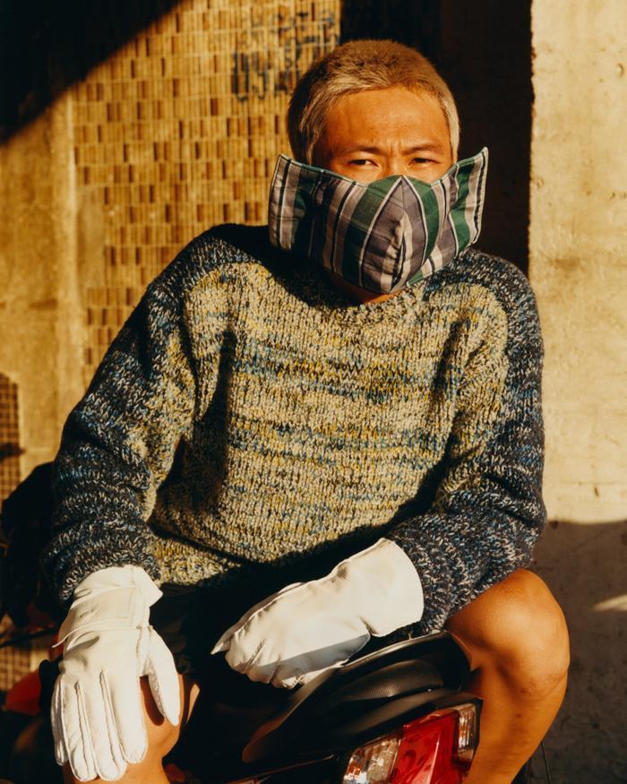 Hoang Nho, 19 tuổi, một chàng trai vận chuyển hoa tại chợ Sài Gòn đang thả dáng trong chiếc áo len 1.950 USD cùng đôi găng tay may riêng và chiếc khẩu trang được mua ở đầu chợ.