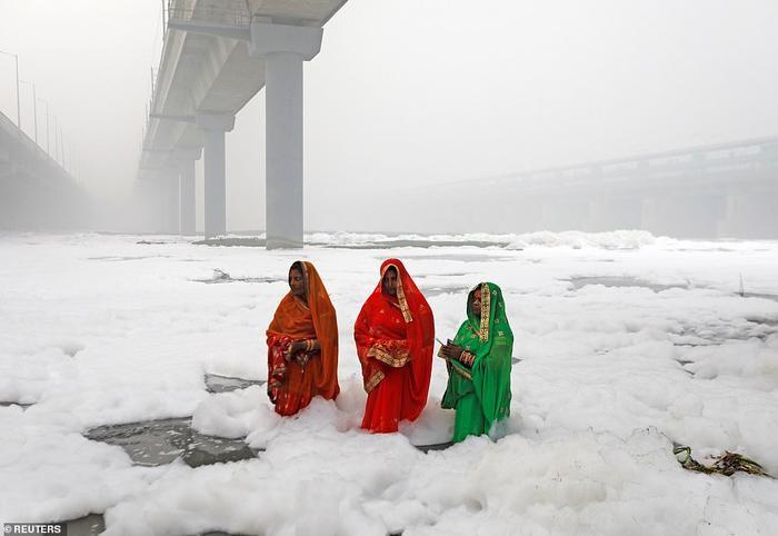 """3 người phụ nữ đứng trong vùng nước ô nhiễm của sông Yamuna trong lễ hội tôn giáo Chatth Puja, xung quanh họ là khói bụi với chỉ số chất lượng không khí hơn 900. Mức 400 là """"trên mức nghiêm trọng""""."""