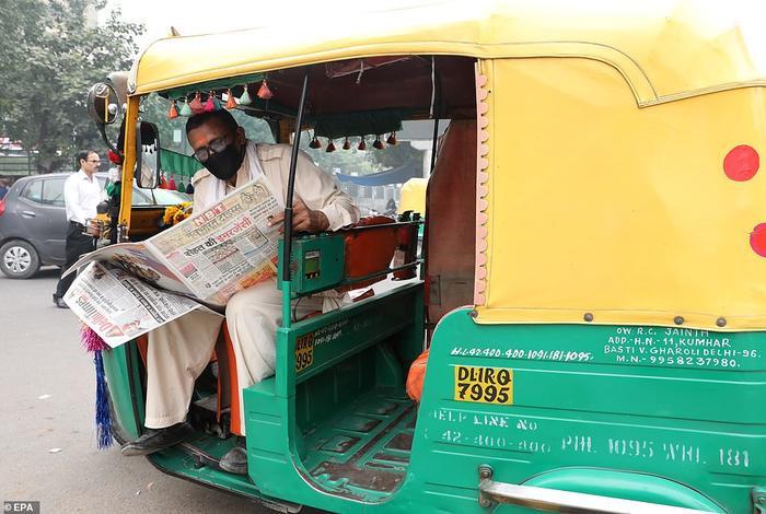 Một người lái xe kéo đeo khẩu trang đọc báo ở thủ đô Delhi. Do tình hình tồi tệ, giới chức thủ đô đã ban bố tình huống khẩn cấp về sức khỏe cộng đồng và nhiều trường học buộc phải đóng cửa.