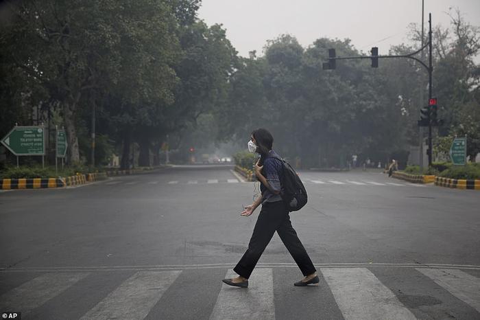 Người dân đeo khẩu trang chống ô nhiễm đi bộ trên đường phố vắng tanh. Nhiều người chọn cách ở trong nhà thay vì ra ngoài vào thời điểm này.