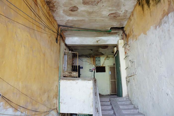 Bên trong khu tập thể, ống nước, dây điện chạy chằng chịt khắp hành lang, cầu thang. Trần nhà ẩm thấp và đóng rêu phong.