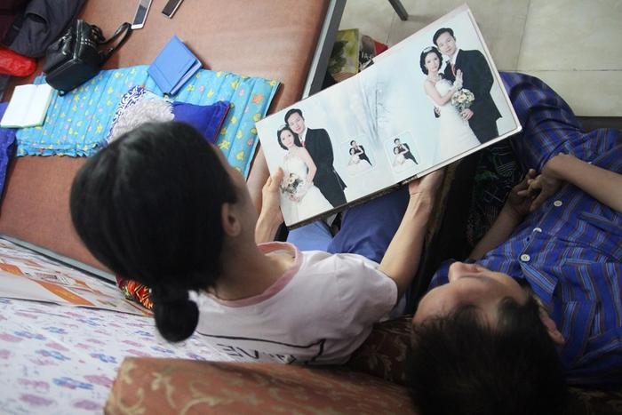 Chị Trang ngồi bên cạnh chồng lật giở từng trang ảnh cưới của hai vợ chồng.