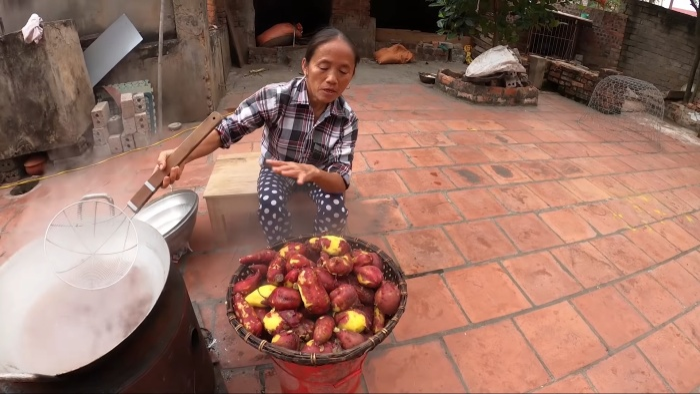 Bà Tân luộc khoai để làm bánh.