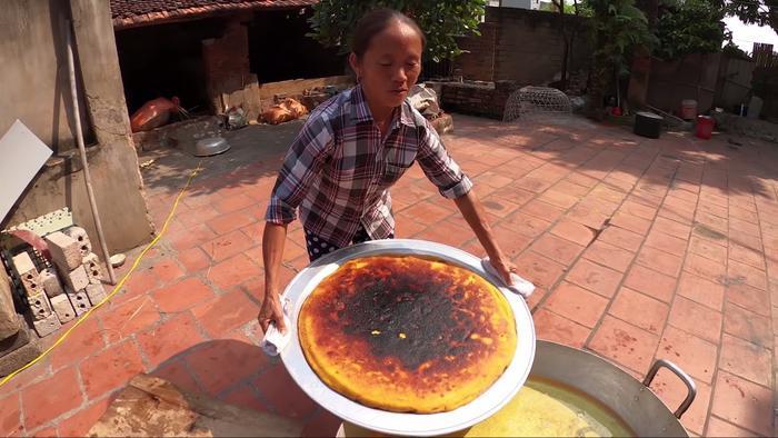 """Thành phẩm không được như ý vì bà Tân đã bất cẩn để quá lửa, khiến chiếc bánh khoai """"siêu to khổng lồ"""" bị cháy đen một mặt."""