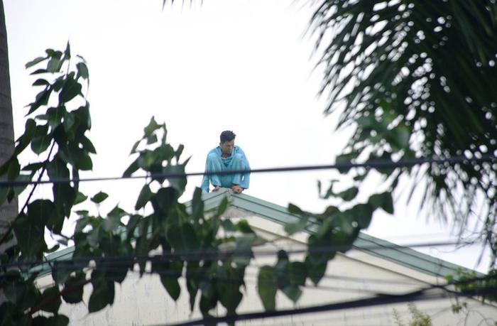 Người đàn ông ngồi trên nóc nhà bệnh viện. Ảnh: báo Pháp Luật TP.HCM