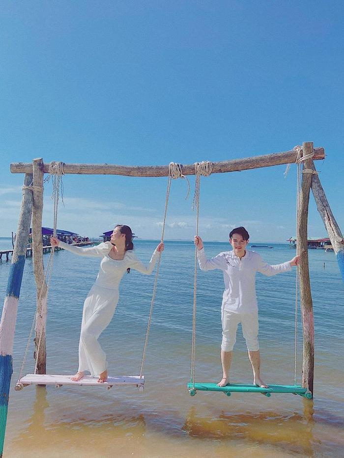 Vợ chồng nữ ca sĩ mặc trang phục trắng đồng điệu, cùng vui đùa với chiếc xích đu trên bờ biển.