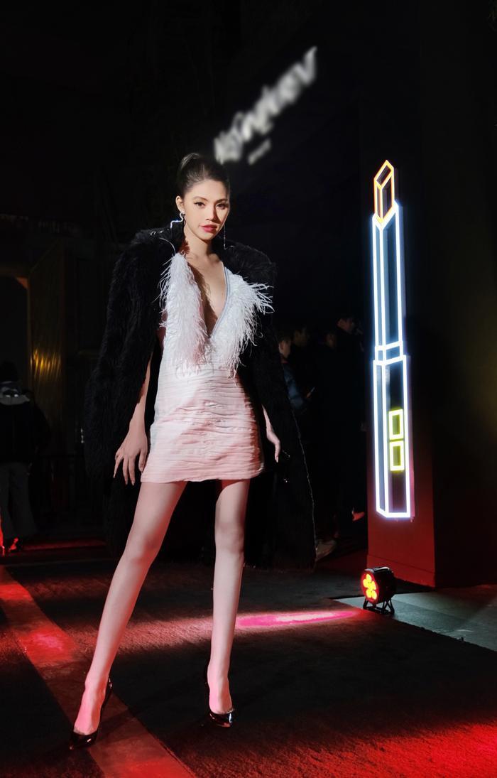 Cô nàng chọn cho mình chiếc váy xẻ ngực sâu mix cùng áo khoác lông phía ngoài,khoe đôi chân dài thon thả.