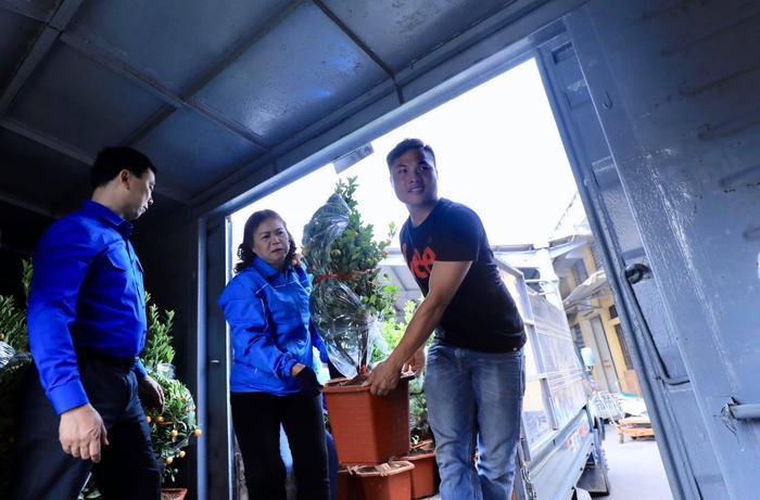 Các tình nguyện viên bê những chậu quất đậm vị Tết được chuyển lên tàu hỏa.