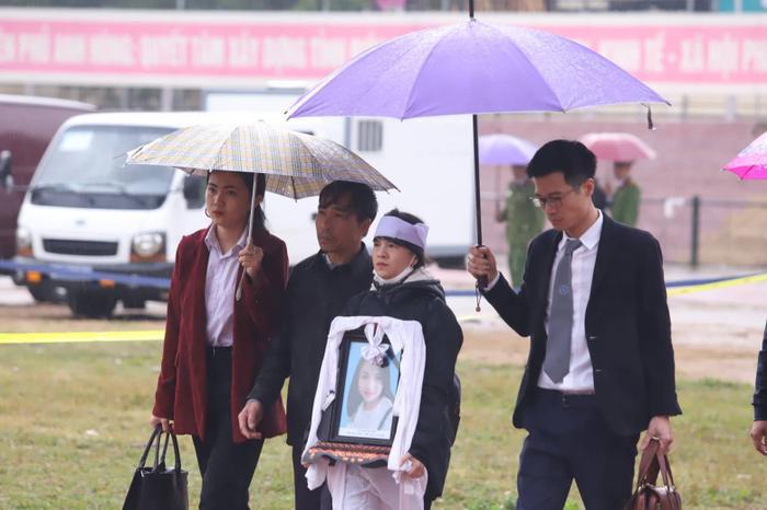 Hai bố con chị Cao Thảo L.đội khăn tang trắng, tay cầm di ảnh em gái đến tòa.