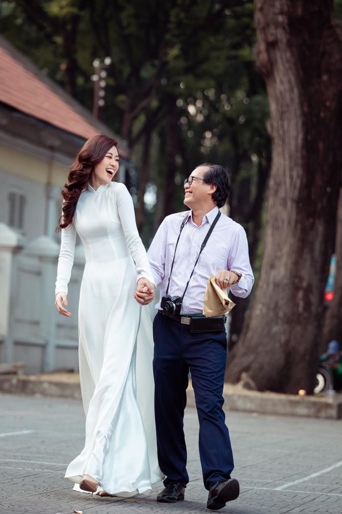 Hoa hậu Khánh Vân diện áo dài trắng đẹp dịu dàng dạo phố cùng bố, tiết lộ về hoa tai may mắn ảnh 1