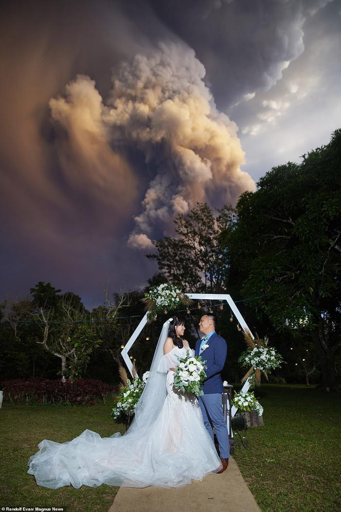 Chino Vaflor và Kat Bautista Palomar tay trong tay mừng ngày thành đôi, mặc cho núi lửa cuồn cuộn phun khói sau lưng.