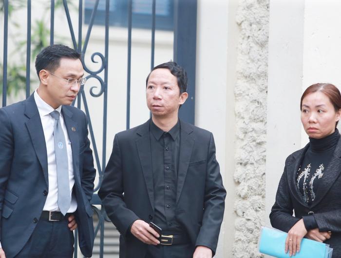 Anh Lê Văn Sơn (bố bé L.) cùng người thân có mặt tại tòa.