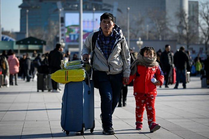 """Khoảng3 tỷ chuyến đi sẽ được thực hiện trong kỳ """"Xuân vận"""" năm nay. Trong ảnh, một người đàn ông dắt bé gái cùng hành lý tới lối vào ga xe lửa Bắc Kinh. Ảnh: AFP"""