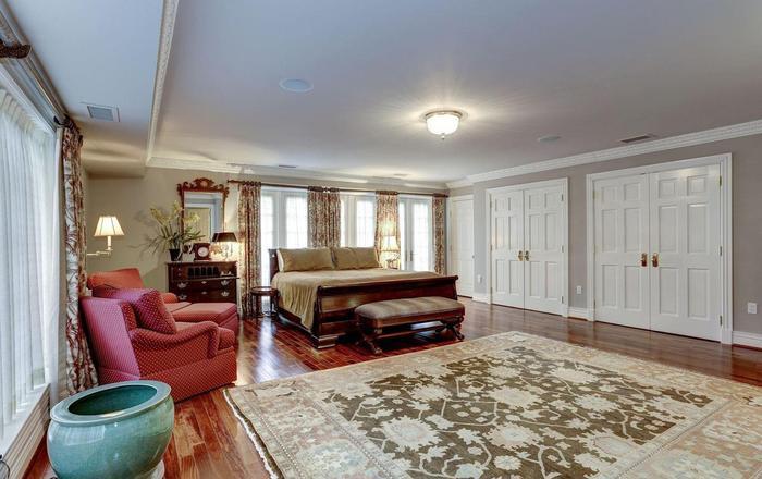 """Phòng ngủ """"siêu to khổng lồ"""" với chiếc giường king-size, bộ sô pha đỏ và thảm trải sản cao cấp. Căn phòng ngủ này còn có thêm một phòng tắm và phòng thay đồ ẩn sau cánh cửa gỗ màu trắng.(Ảnh: Redfin)"""