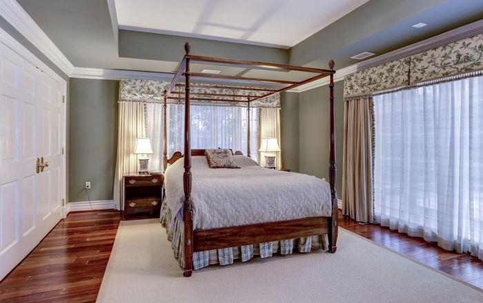 Phòng ngủ dành cho khách cũng không kém cạnh với sàn gỗ đắt tiền, view nhìn ra khung cảnh bên xung quanh biệt thự.(Ảnh: Redfin)