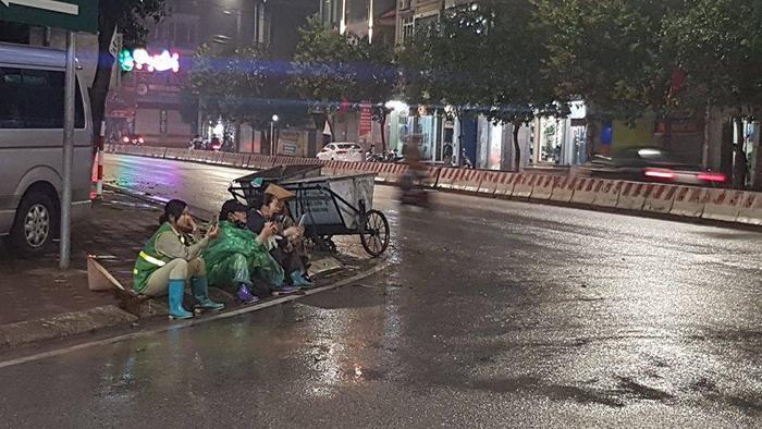 Một số nữ lao công ngồi nghỉ ngơi bên lề đường. Có lẽ rằng họ đang cầm điện thoại để tranh thủ gọi điện về cho gia đình. Ảnh Facebook Tam ngo
