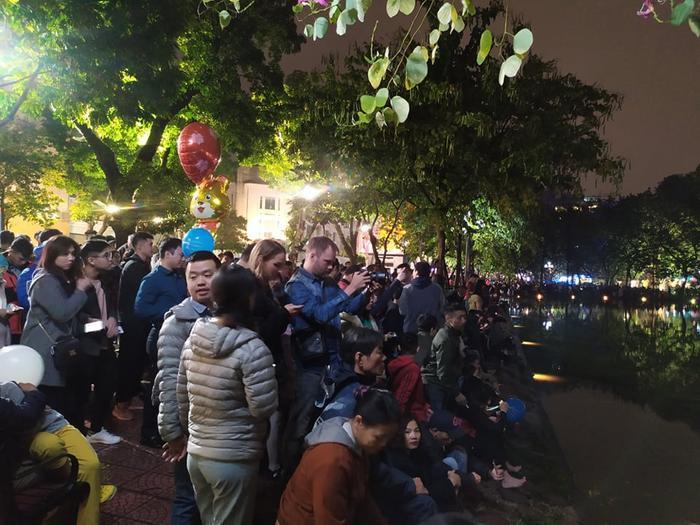 Nhiều người dân cùng người thân, bạn bè có mặt tại Hồ Gươm bất chấp cái lạnh sau cơn mưa để chiêm ngưỡng pháo hoa trong giờ phút thiêng liêng đón năm mới.