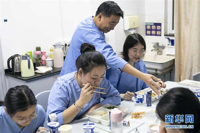 """Đội ngũ các nhân viên y tế đang tranh thủ ăn cơm để tiếp tục chăm sóc bệnh nhân. Có lẽ đối với họ, giờ phút này được ngồi ăn bữa cơm """"đàng hoàng"""" như thế này đã là tốt lắm rồi. Ảnh Tân Hoa Xã"""