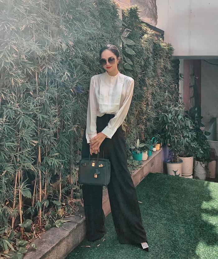 Trong khi đó, Hoa hậu Hương Giang nền nã hơn với quần ống suông, áo sơ mi cách điệu phối cùng chiếc túi xách đắt đỏ.