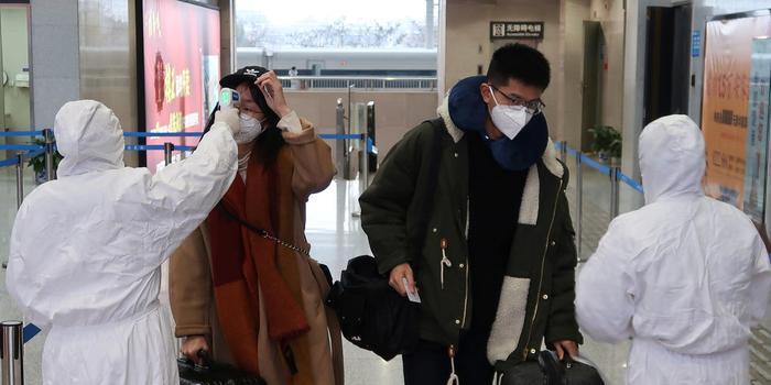 Đội ngũ y tế mặc đồ bảo hộ kiểm tra thân nhiệt của hành khách đến ga Hàm Ninh, Hồ Bắc, Trung Quốc vào thứ Sáu tuần trước. (Ảnh: Reuters)
