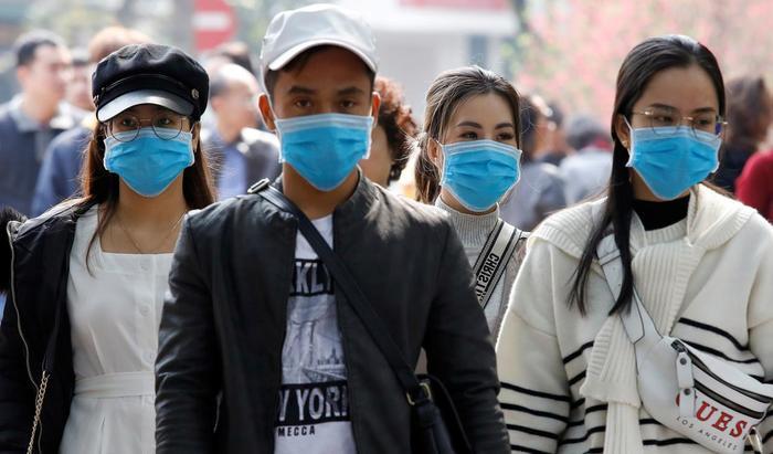 Người dân đeo khẩu trang khi đang tản bộ tại Hồ Hoàn Kiếm, Hà Nội để phòng ngừa virus corona. (Ảnh:REUTERS/Kham)