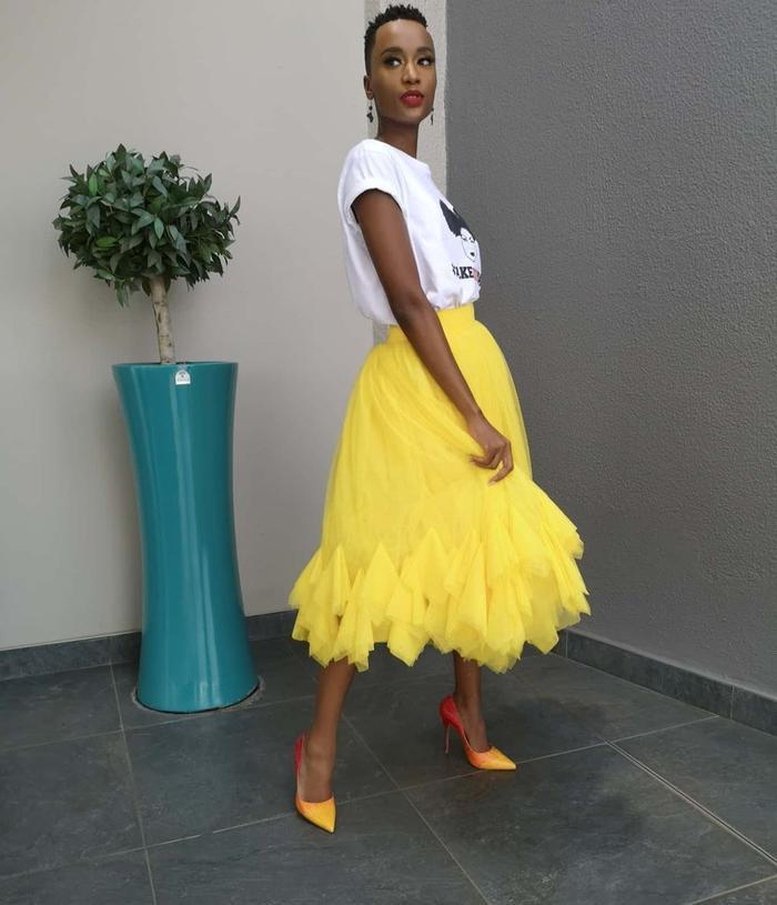 Zozibini Tunzi kết hợp áo thun với chân váy vàng rực rỡ.