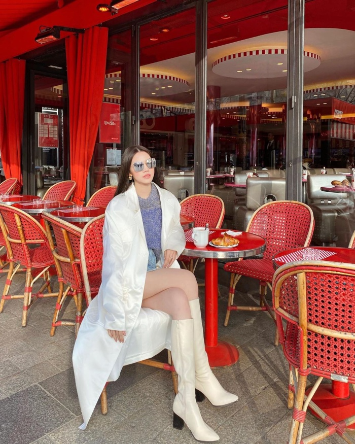 Jolie Nguyễn mang đến cây đồ với tông trắng cá tính,áo khoác dài và váy ngắn tưởng chừng là sự kết hợp tương phản nhưng hóa ra lại cực kỳ ăn rơ.