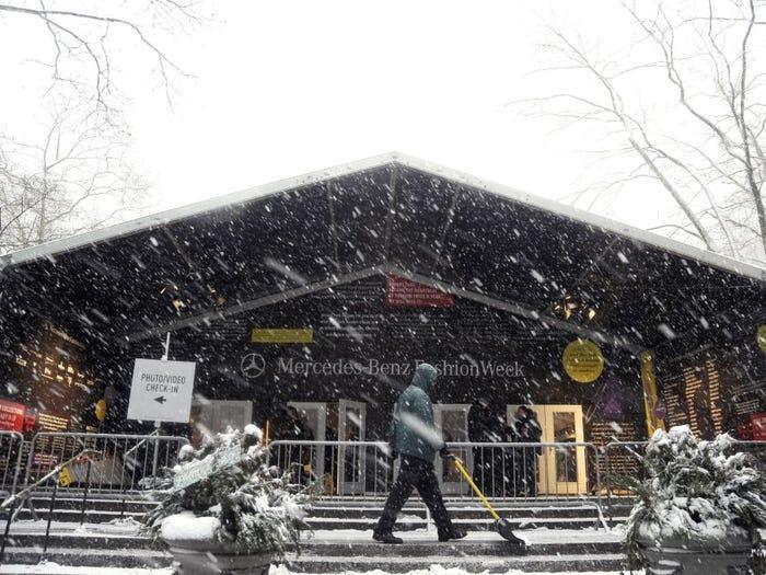 Khi có tuyết hoặc mưa, không ai còn muốn trưng diện đến một buổi diễn thời trang cả. Người đàn ông này phải làm việc liên tục dưới trời lạnh để quét tuyết trên bậc thang ở địa điểm tổ chức.