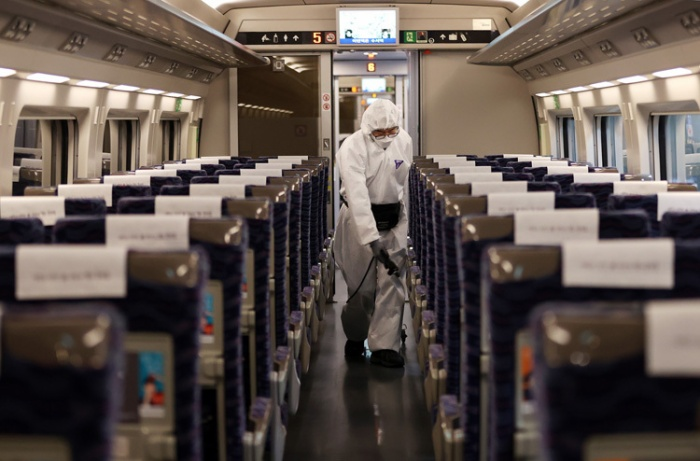 Nhân viên y tế khử trùng tàu cao tốc KTX tại ga Suseo, Seoul, Hàn Quốc ngày 25/2. Ảnh: Reuters.