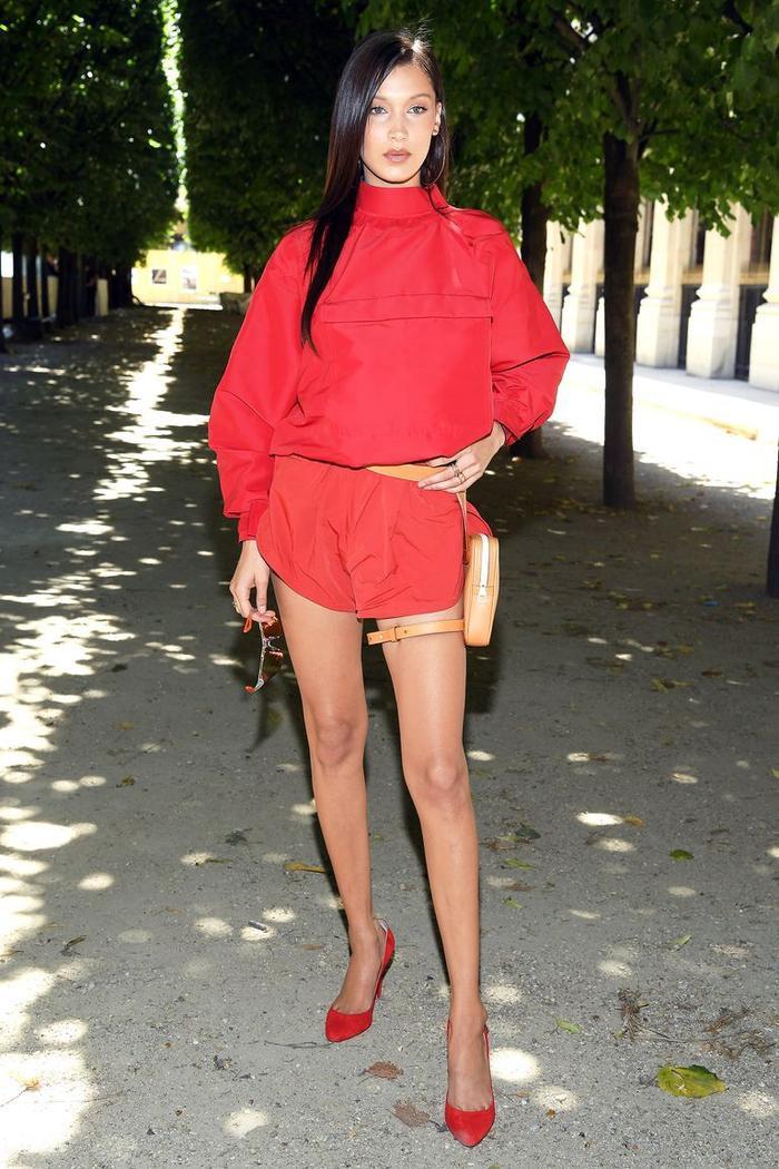 Siêu mẫu tham dự buổi trình diễn thời trang nam Louis Vuitton tại Paris trong bộ đồ romper màu đỏ, túi thắt lưng màu da và giày cao gót mũi nhọn.