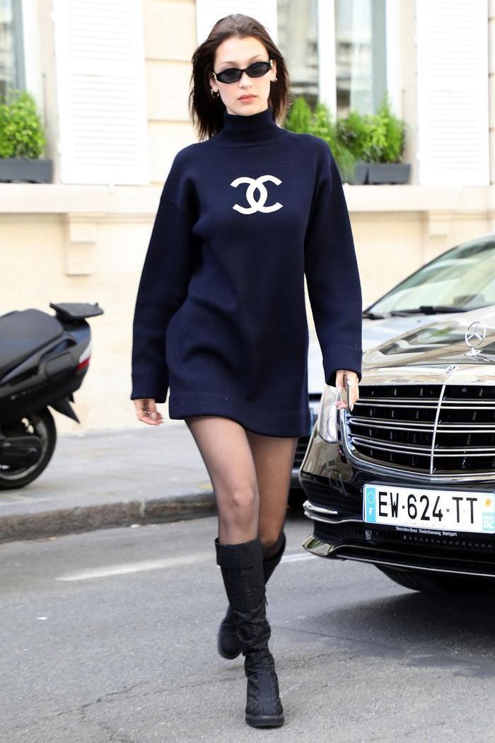 Bella mặc một chiếc váy ngắn màu đen của Chanel, quần tất đen trong suốt, bốt cao đến đầu gối và đeo kính râm Le Specs x Jordan Askill khi đi chơi ở Paris.