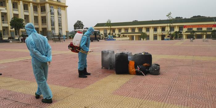 Nhân viên khử trùng hành lý ở khoảng sân rộng.