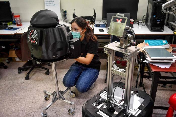 Một nữ sinh đang lắp đặt robot ninja tạiTrung tâm Công nghệ Robotics thuộc Đại học Chulalongkorn ở Bangkok. (Ảnh: Lillian SUWANRUMPHA / AFP)