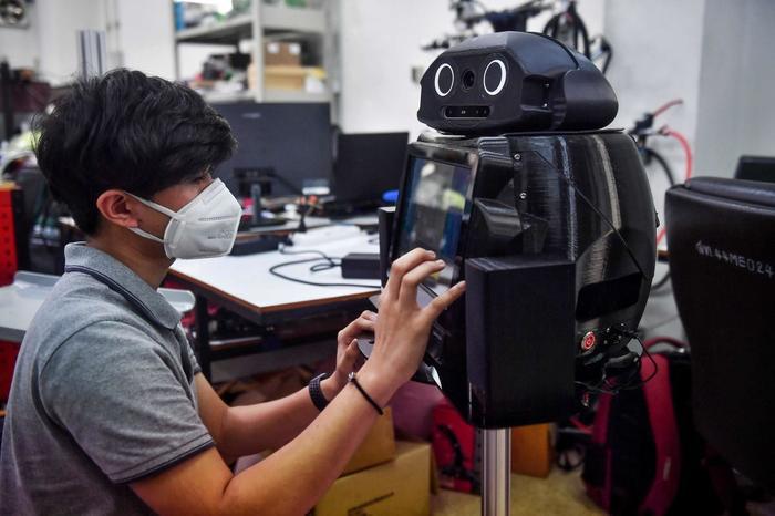 Một sinh viên kỹ thuật Thái Lan đang cài đặt phần mềm cho một chú robot ninja được dùng để sàng lọc và quan sát bệnh nhân nhiễm virus corona tại Trung tâm Công nghệ Robotics thuộc Đại học Chulalongkorn ở Bangkok. (Ảnh: Lillian SUWANRUMPHA / AFP)