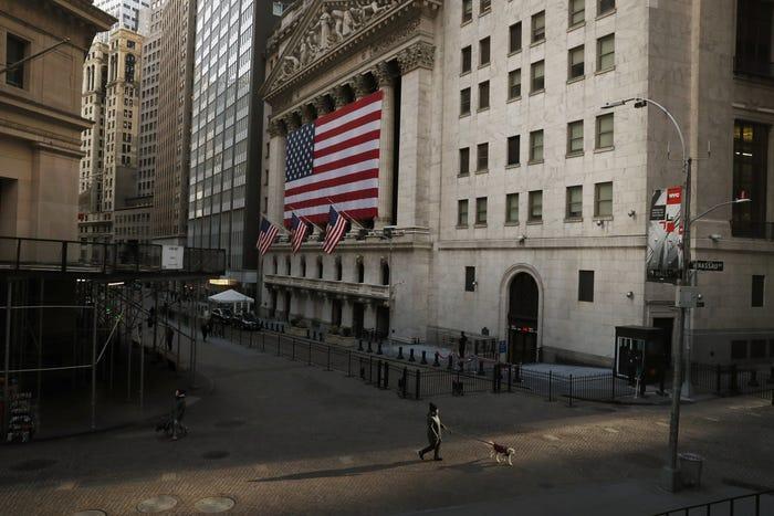 Một người đi bộ trước khu vựcSàn giao dịch chứng khoán New York (NYSE) trên Phố Wall. Lo ngại tình hình dịch bệnh đã khiến nhiều người Mỹ chọn ở nhà.