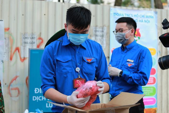 Các sinh viên tình nguyện mở gói đồ cẩn thận.