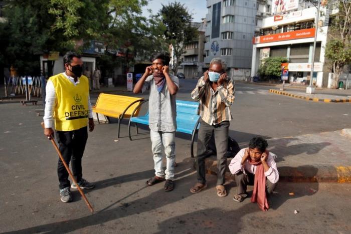 3 người bị phạt đứng lên ngồi xuống ởAhmedabad, Ấn Độ ngày 24/3 do vi phạm lệnh phong tỏa vì COVID-19. Ảnh: Reuters
